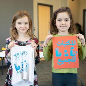 "Two girls holding newly-printed ""libraries are for everyone"" shirts"
