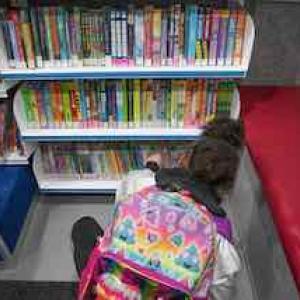 Girl looking at bookshelf