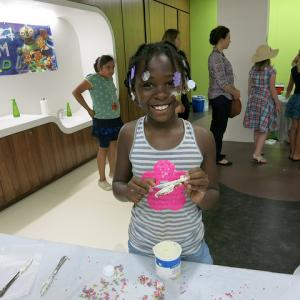 smiling child showing off craft they created