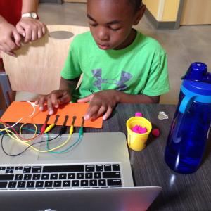child playing with Makey Makey