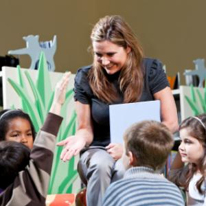 woman reading a book to a group of children at storytime