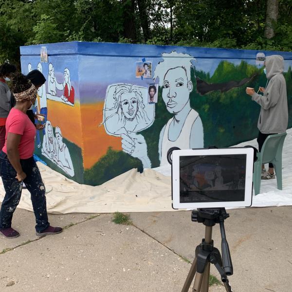 Students and artist Emida Roller work on the shelter mural