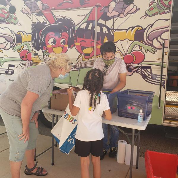 Kids pick out books at the Dream Bus