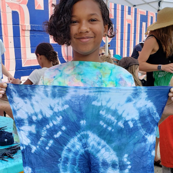 Young kid holding cloth dyed with indigo dye during an Arts in the Alley event