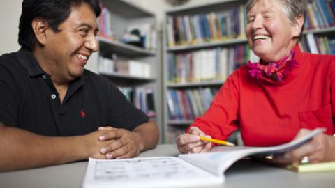 an adult tutoring another adult in a library