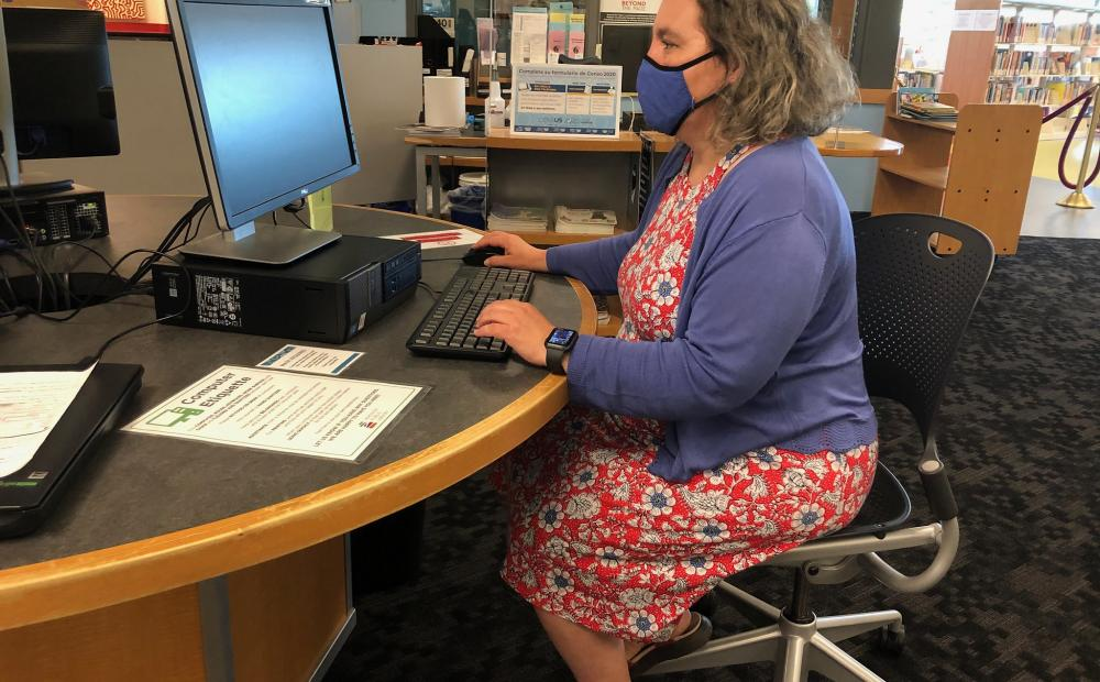 A masked patron uses a public computer at a Madison Public Library location