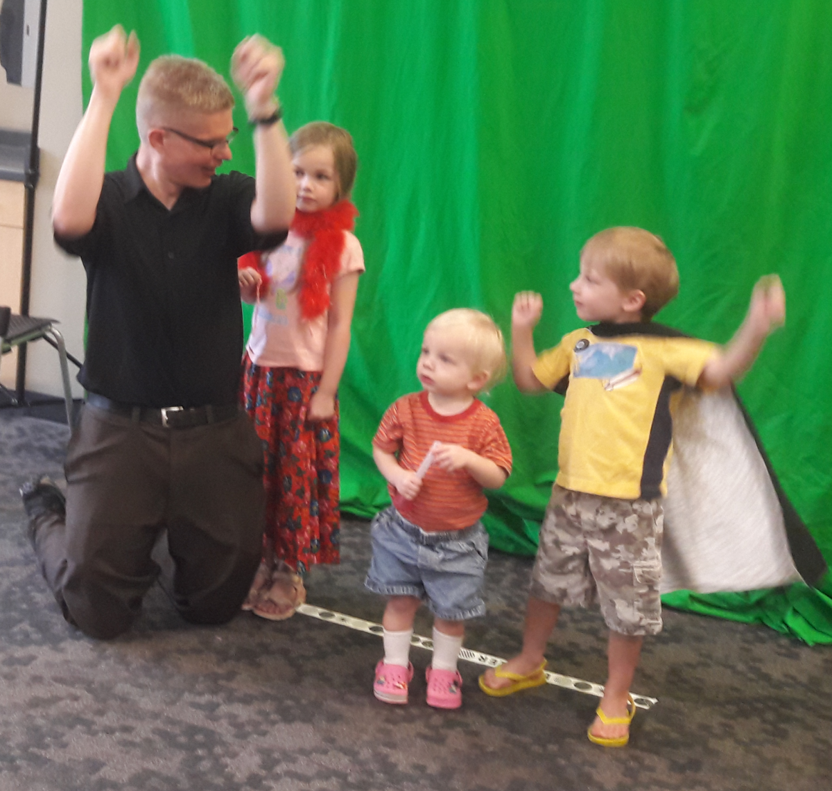 group of kids recording a music video at the library in front of a green screen