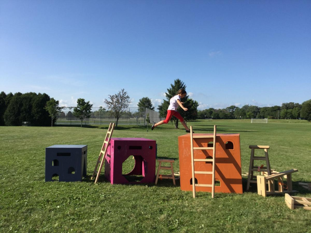 Young child jumps from Anji Play equipment in Reindahl Park