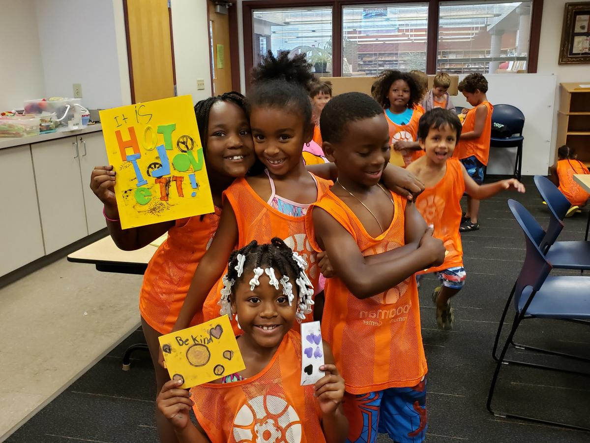 Kids hold up their stamp-making creations