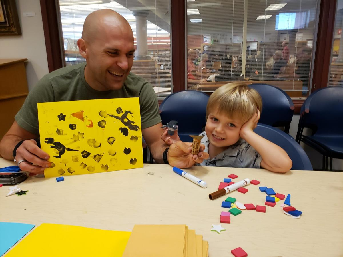Parent and child show off their stamp-making creation