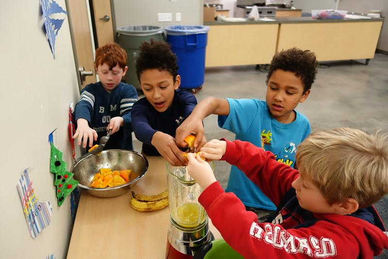 Chef Lily's students juice oranges for one of her recipes during cooking class
