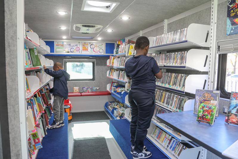 Two African-American boys peruse books on the Dream Bus Library