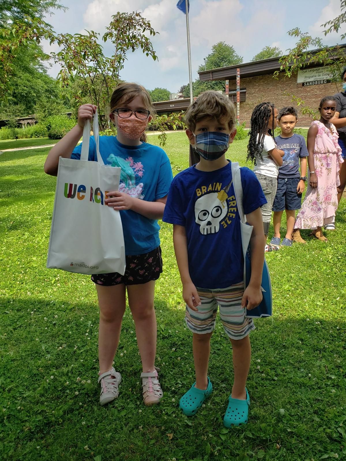 Two masked students at Sandburg Elementary get their books