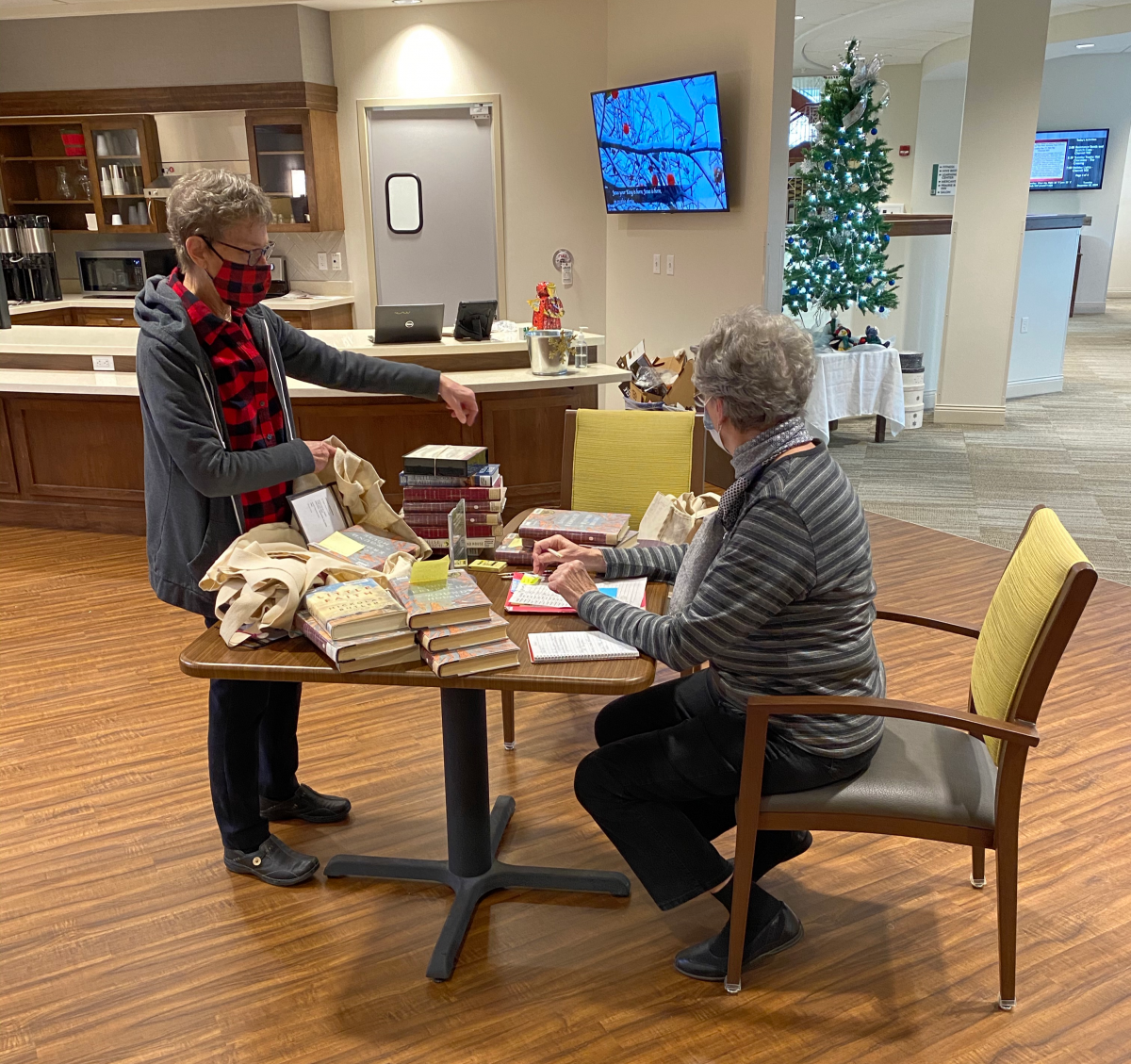 Resident volunteers at Oak Village Prairie Ridge process books for their facility mini-library