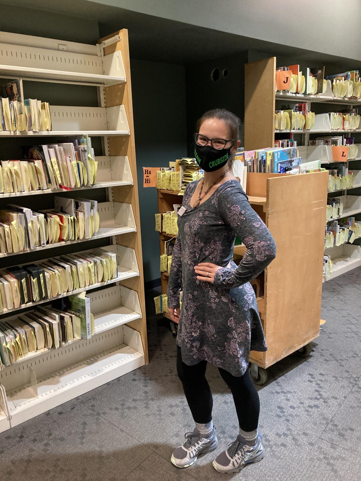 Library clerk Victoria shows off the full hold shelves at Sequoya