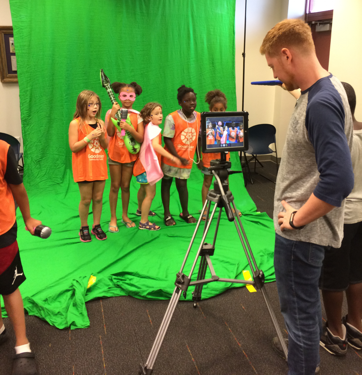 group of girls recording a music video at the library in front of a green screen