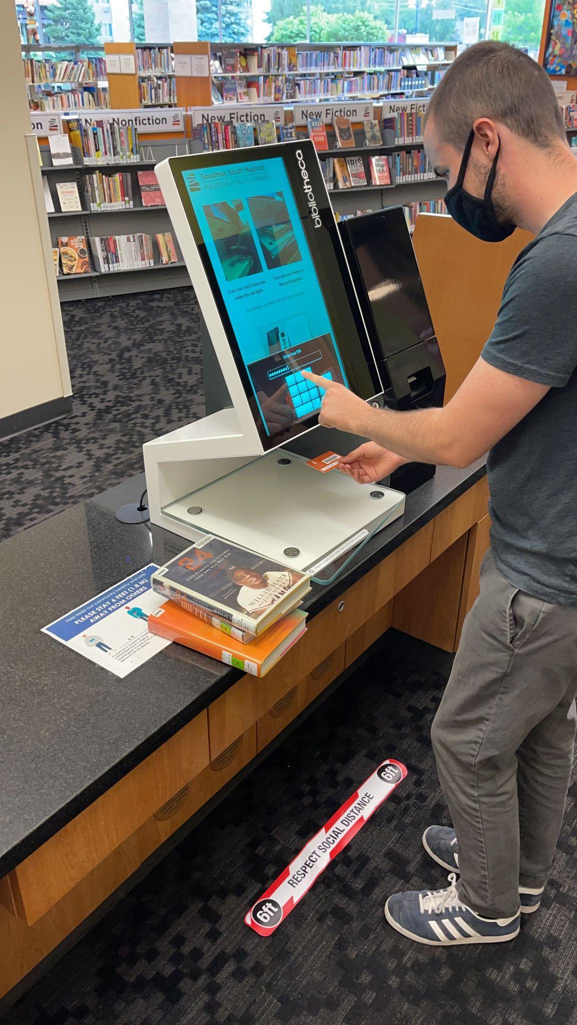 A patron checks out using a self-check machine at Goodman South Madison Library
