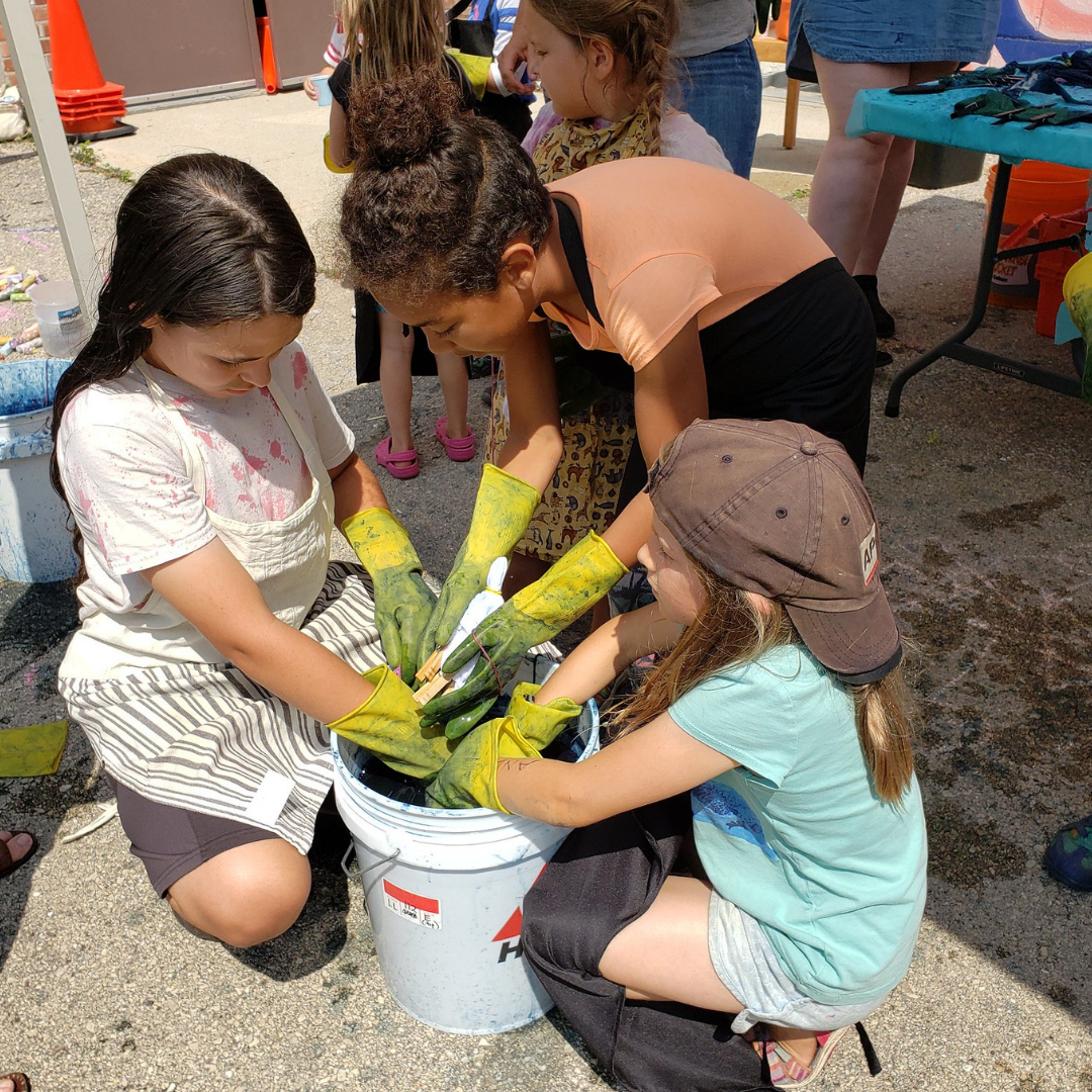 Kids reaching into a bucket of indigo dye during an Arts in the Alley event