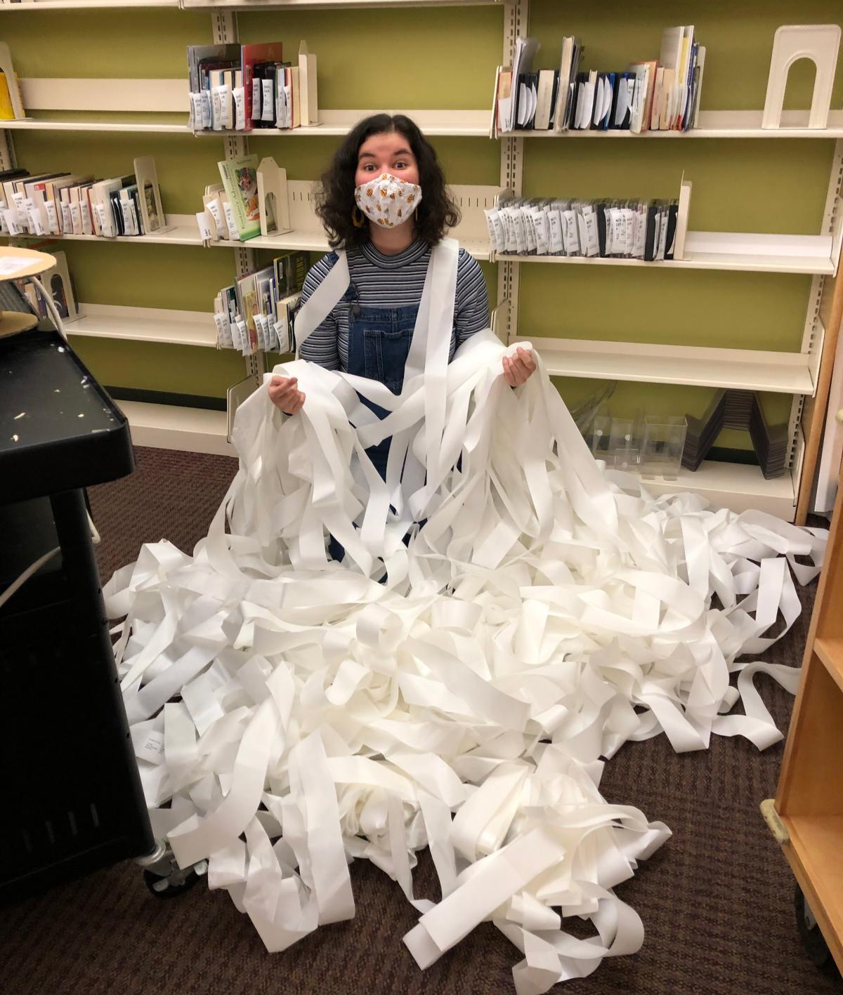 Library Assistant Hannah Majeska poses with completed RFID tags at Lakeview Library
