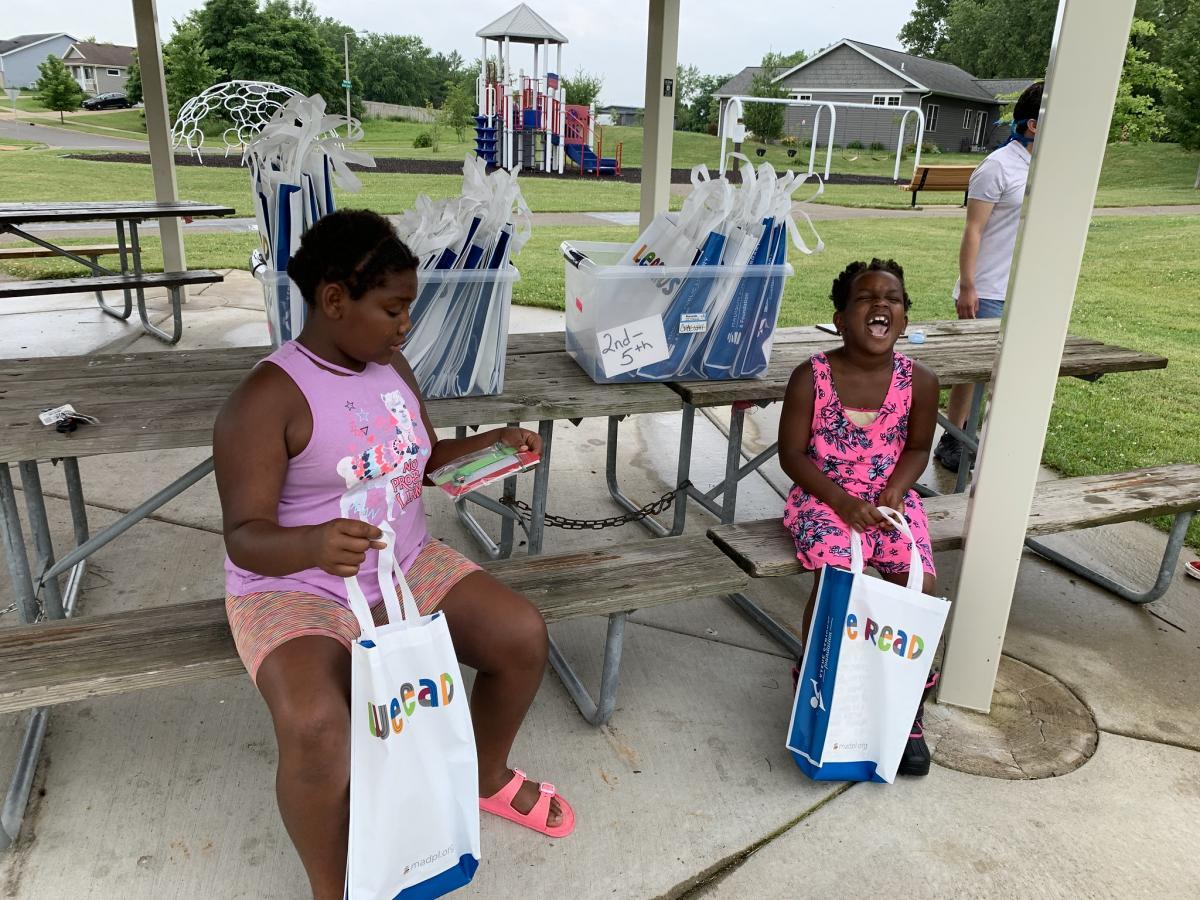 Two girls enjoy their Dream Bus books