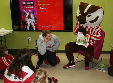 Bucky Badger reading to children during storytime
