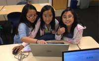 Three young kids learning how to code in front of a computer.