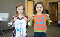 Two young kids holding prints that read Libraries Are for Everyone