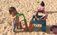 Two toddlers play in the sand at Haen Family Park