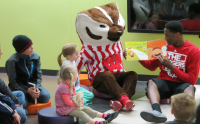 Bucky Badger and a UW Athlete read to kids at the library